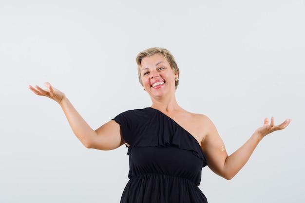 Piękna kobieta pozuje jak pokazuje coś na rękach w czarnej bluzce i wygląda zadowolona