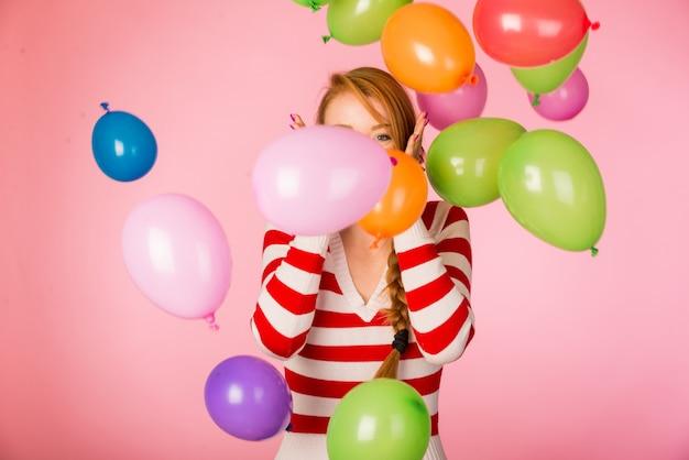 Piękna kobieta pozuje na menchii ścianie z balonami