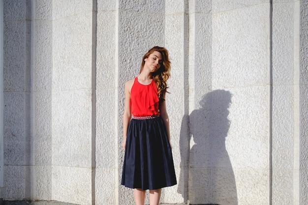 Piękna kobieta pozuje na miastowej ścianie
