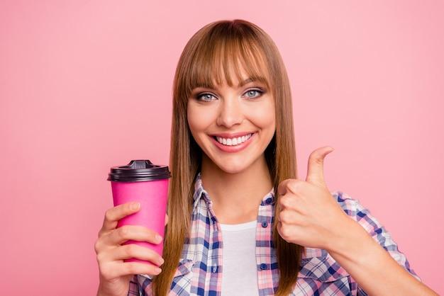 Piękna kobieta pozuje na różowej ścianie