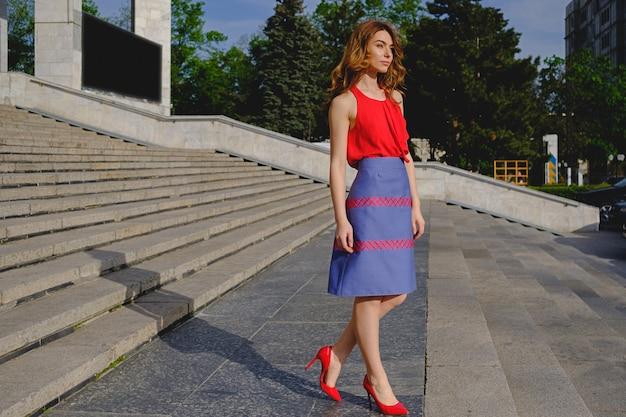 Piękna kobieta pozuje na schodkach