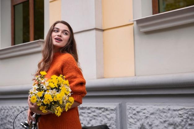 Piękna kobieta pozuje na zewnątrz z bukietem kwiatów i rowerów
