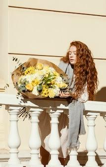 Piękna kobieta pozuje na zewnątrz z bukietem wiosennych kwiatów