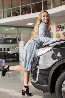 Piękna kobieta pozuje obok samochodu