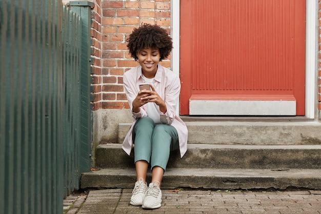 Piękna kobieta pozuje poza jej telefonem