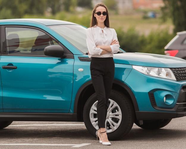 Piękna kobieta pozuje przed nowożytnym samochodem