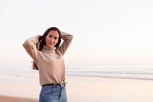 Piękna kobieta pozuje przy plaży z miejsca na kopię