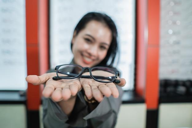 Piękna kobieta pozuje trzymając okulary na tle gabloty na okulary w klinice okulistycznej