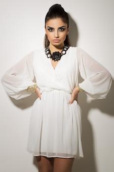 Piękna kobieta pozuje w biel sukni
