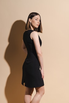 Piękna kobieta pozuje w czarnej sukience