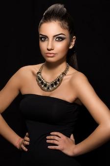 Piękna kobieta pozuje w czerni sukni