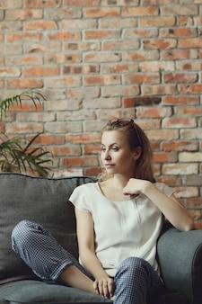 Piękna kobieta pozuje w kanapie, wnętrze dom