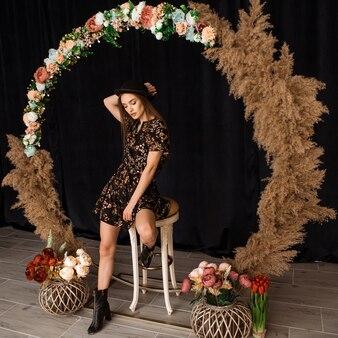 Piękna kobieta pozuje w kręgu posuszu w sukience z nadrukiem kwiatowym w studio