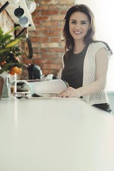 Piękna kobieta pozuje w kuchni z magazynem