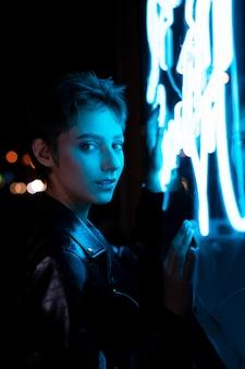 Piękna kobieta pozuje w nocy w niebieskim neonowym świetle