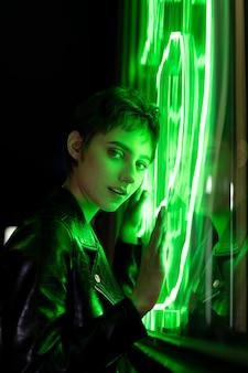 Piękna kobieta pozuje w nocy w zielonym neonowym świetle