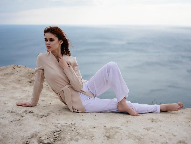 Piękna kobieta pozuje w pobliżu skał w eleganckim stylu piasku