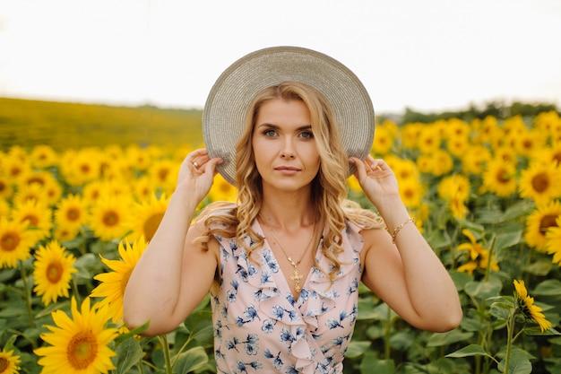 Piękna kobieta pozuje w polu uprawnym ze słonecznikiem w słoneczny letni dzień