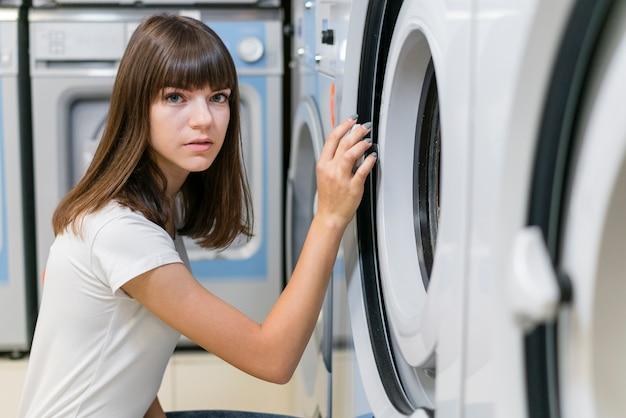 Piękna kobieta pozuje w pralnianym pokoju