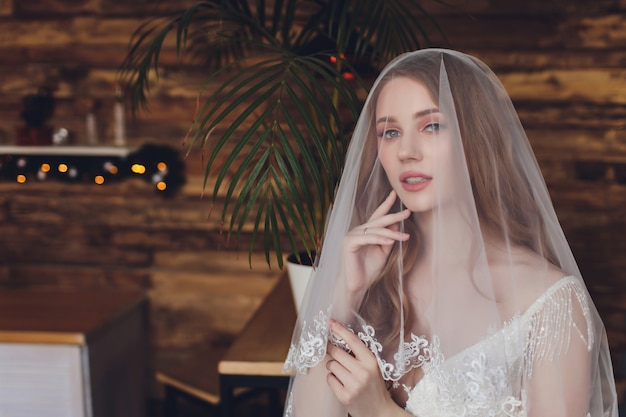 Piękna kobieta pozuje w ślubnej sukni.