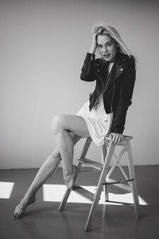 Piękna kobieta pozuje w stylowych ubraniach z czarno-białym efektem