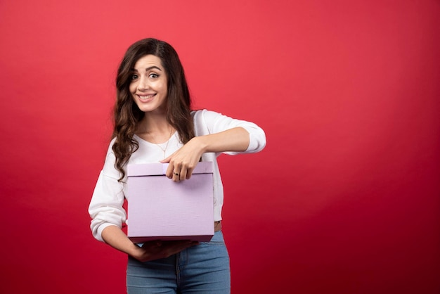 Piękna kobieta pozuje z fioletowym pudełkiem. zdjęcie wysokiej jakości