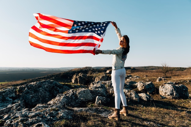 Piękna kobieta pozuje z flaga amerykańską na górze góry