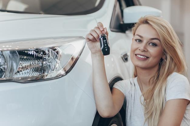 Piękna kobieta pozuje z jej nowym samochodem przy przedstawicielstwem handlowym