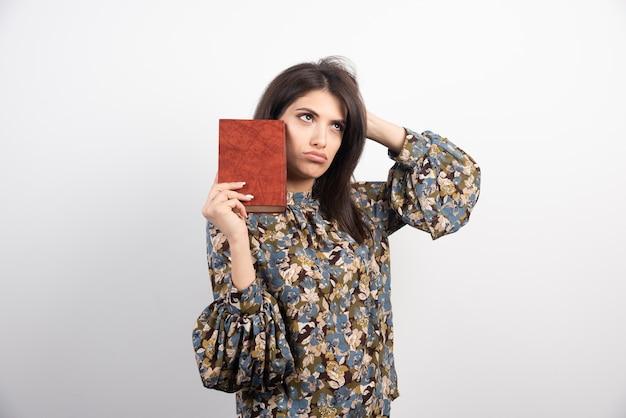 Piękna kobieta pozuje z książką na białym tle.
