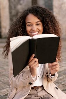Piękna kobieta pozuje z książką w jej ręce outdoors