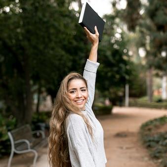 Piękna kobieta pozuje z książką w jej ręce outside