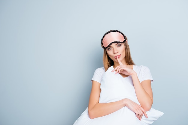 Piękna kobieta pozuje z maską snu i poduszką