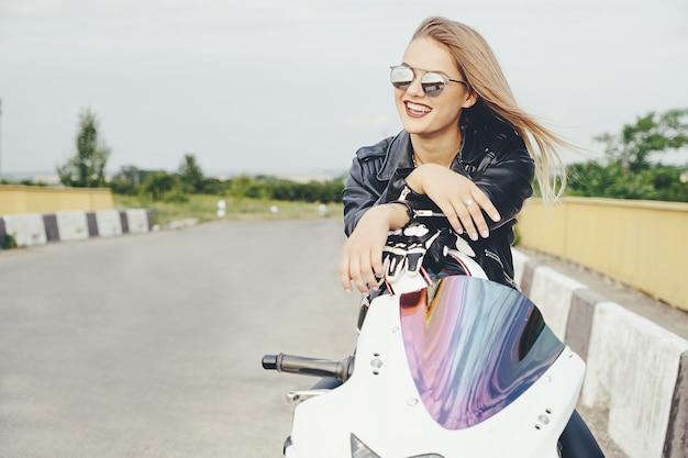 Piękna kobieta pozuje z okularami przeciwsłonecznymi na motocyklu