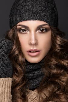Piękna kobieta pozuje z stylową fryzurą i uzupełniał