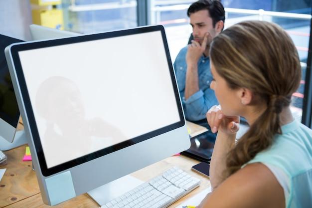 Piękna kobieta pracuje na komputerze stacjonarnym