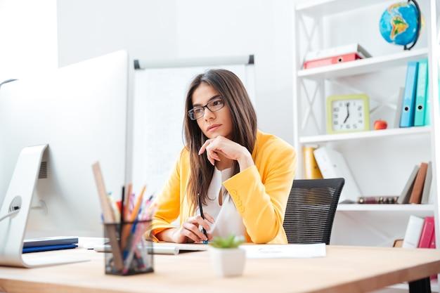 Piękna kobieta pracuje na komputerze w biurze