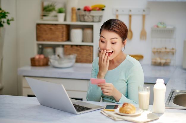 Piękna kobieta pracuje w biurze za pomocą laptopa i karty kredytowej zasłaniając usta ręką