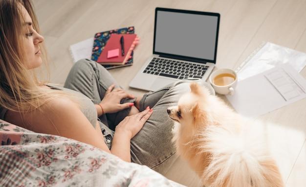 Piękna kobieta pracuje w domu. pies jej pomaga. w pobliżu siedzi szpic pomorski.