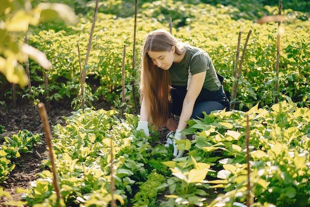 Piękna kobieta pracuje w ogrodzie w pobliżu domu