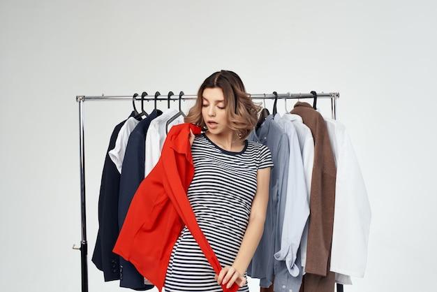 Piękna kobieta próbuje na jasnym tle czerwonej koszuli. zdjęcie wysokiej jakości