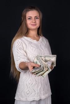 Piękna kobieta, proponując pieniądze lub łapówkę na białym tle na czarnej ścianie