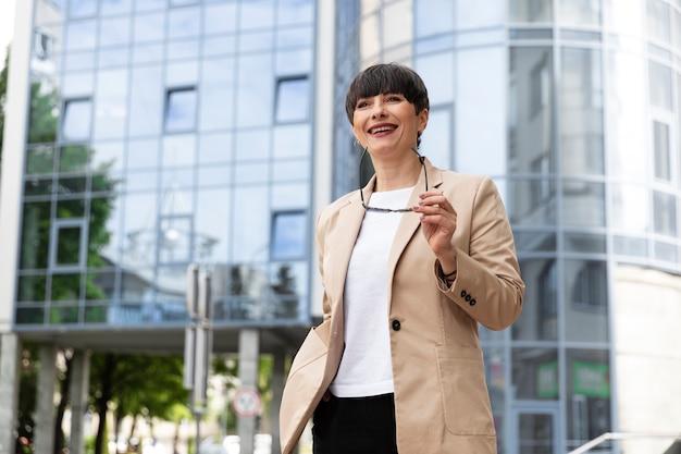 Piękna kobieta przed szklanym budynkiem