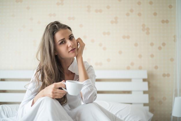 Piękna kobieta przy jej sypialnią pije kawę w ranku