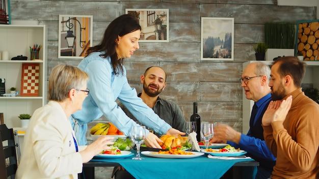 Piękna kobieta przybywająca z smacznym obiadem z pieczonym kurczakiem. przyjaciele i rodzina zebrali się razem na uroczystości