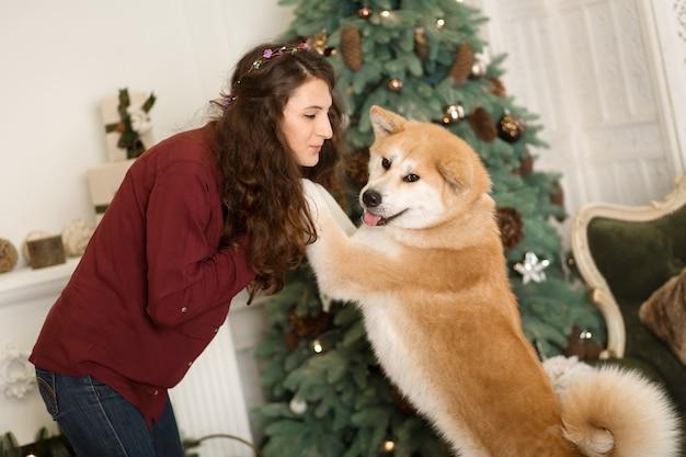 Piękna kobieta przytula, przytula swojego psa akita inu.