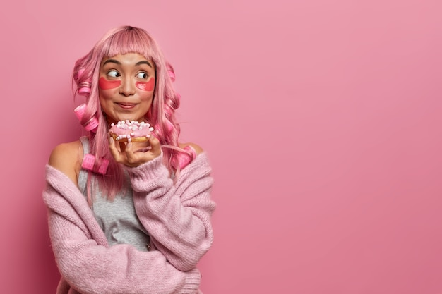 Piękna kobieta rasy mieszanej ma różowe włosy, potargane grzywki, nosi podkładki upiększające, aby zredukować zmarszczki, delektuje się pysznym glazurowanym pączkiem, tworzy fryzurę