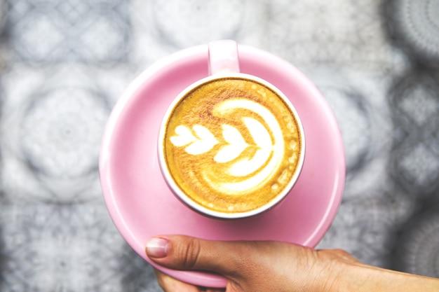 Piękna kobieta ręka trzyma kubek gorącej kawy latte nad podłogą sztuki jako tło.