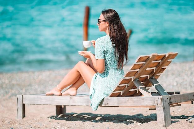 Piękna kobieta relaks podczas egzotycznych wakacji na plaży, ciesząc się słodką kawą