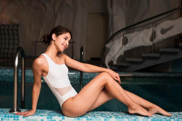 Piękna kobieta relaksuje basenem przy zdrojem