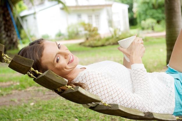 Piękna kobieta relaksuje na hamaku z kawą